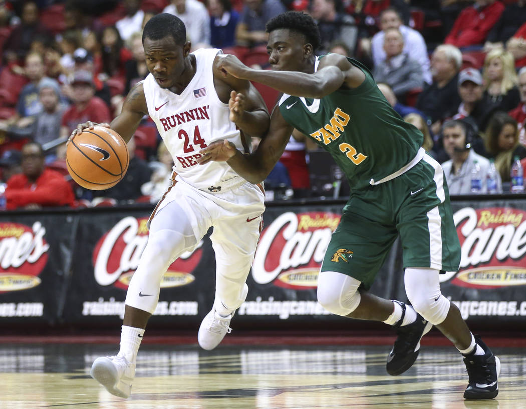 UNLV's Jordan Johnson (24) drives the ball against Florida A&M's Kamron Reaves (2) during their basketball game at the Thomas & Mack Center in Las Vegas on Saturday, Nov. 11, 2017. Chase S ...