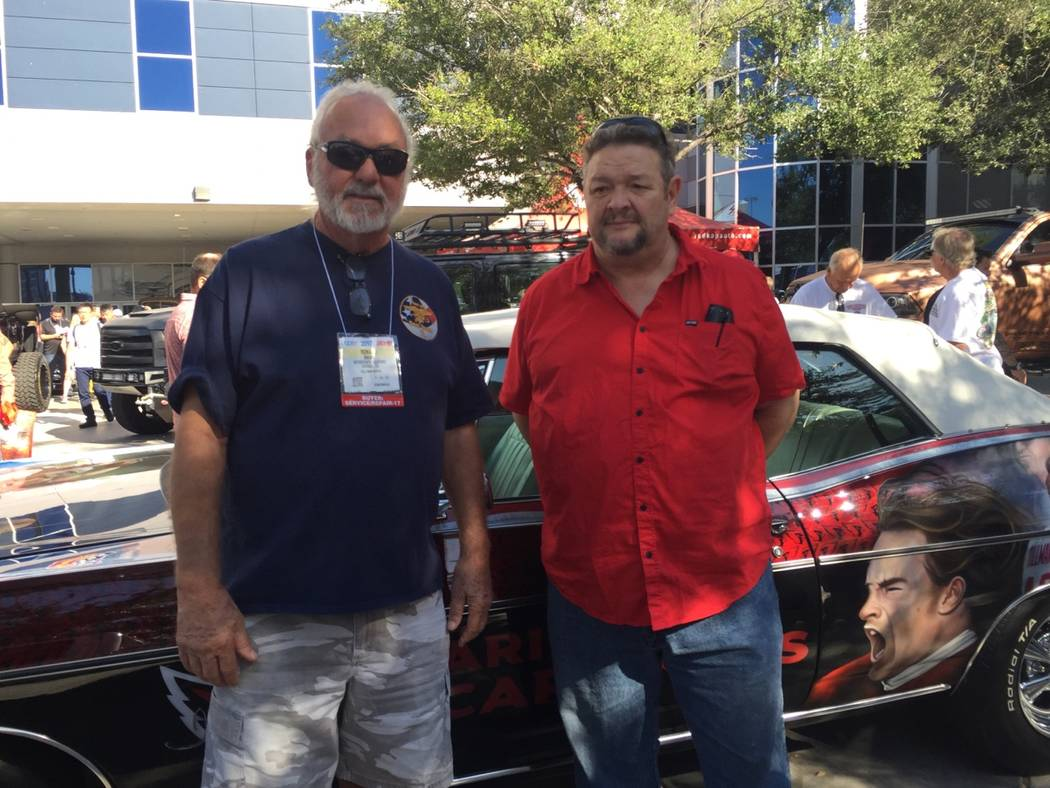 Veterans advocate Ronnie Rains, left, and airbrush artist Mickey Harris are shown with Pat Tillman's restored 1968 Chevy Impala convertible at the SEMA show at the Las Vegas Convention Center. (co ...