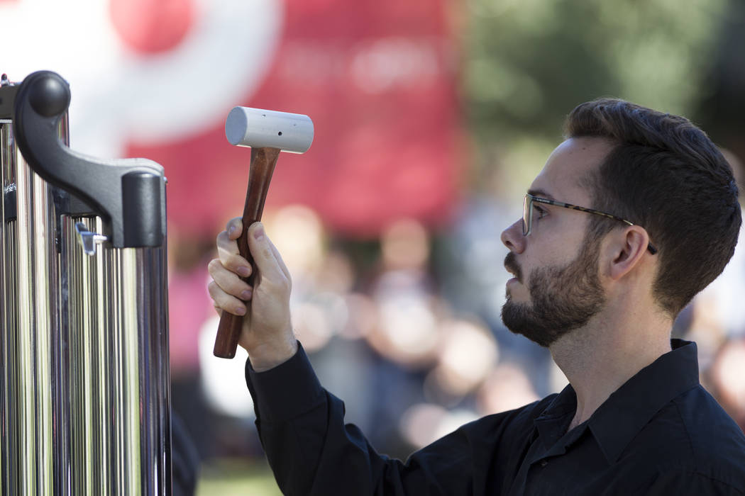 Marcus LeBlanc, graduate student at UNLV, rings a chime for each person who died at the Route 91 Harvest Festival during a remembrance ceremony for the mass shooting victims at UNLV in Las Vegas,  ...