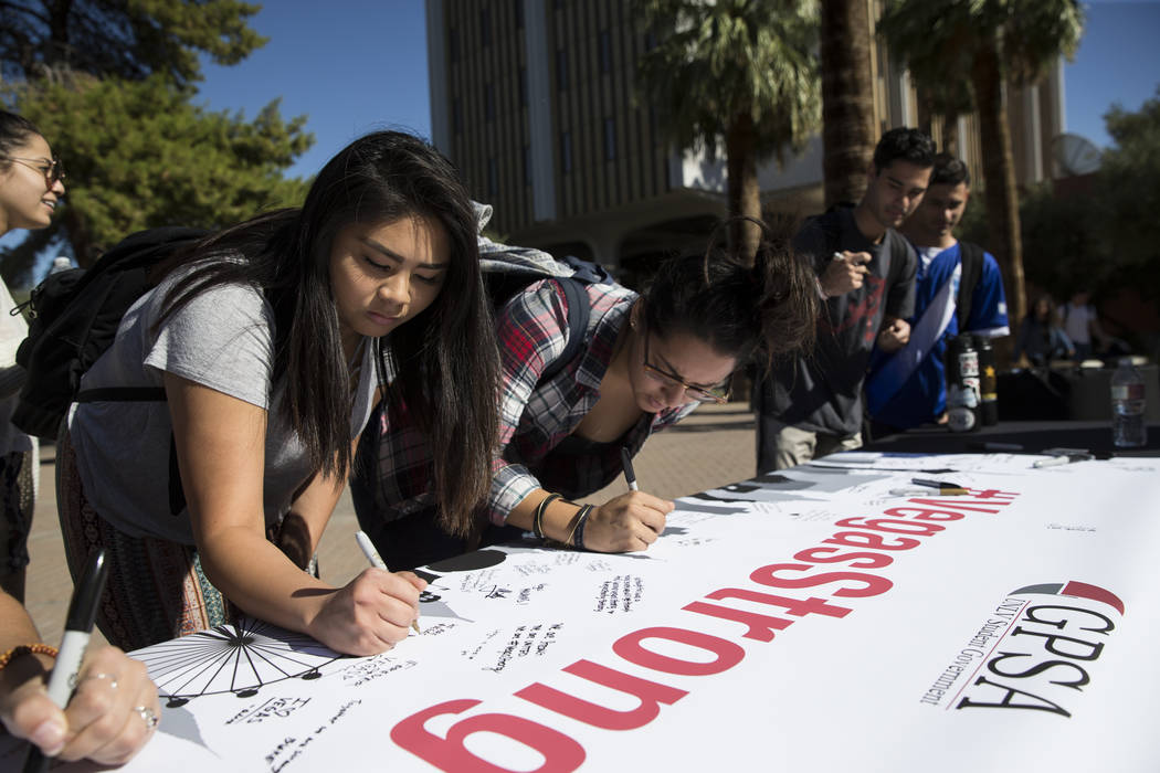 UNLV students Shealyn Ladao, left, and Heaven Lucero, sign a Vegas Strong banner during a remembrance ceremony for the mass shooting victims at UNLV in Las Vegas, Thursday, Nov. 2, 2017. Erik Verd ...