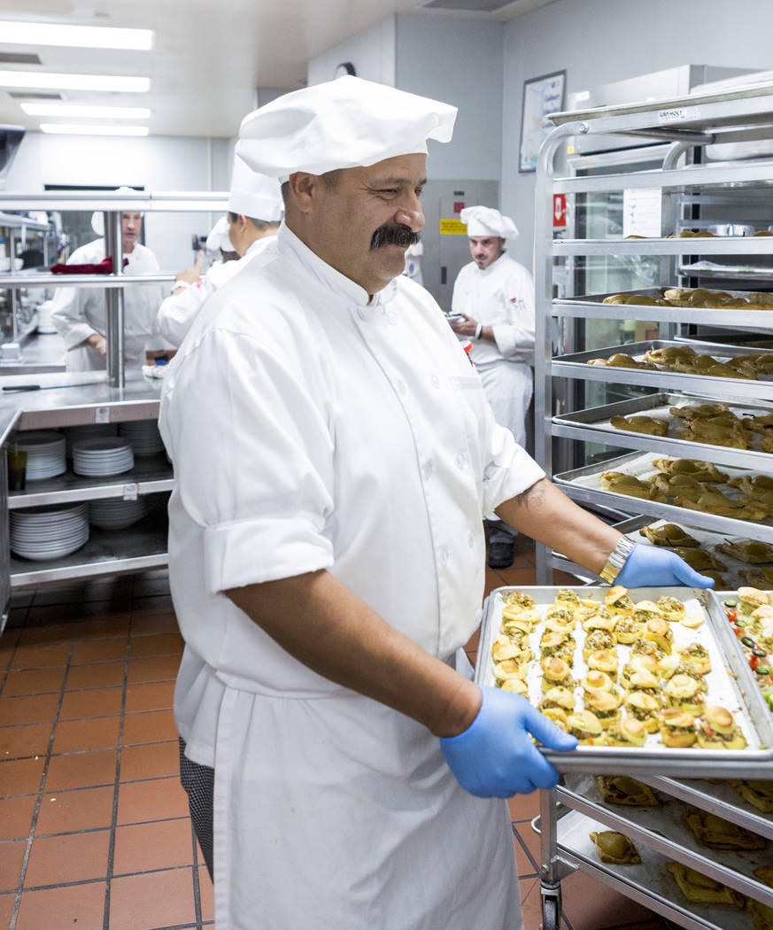 Graduate of the Salvation Army Culinary Arts Program John Fierro carries a tray of food during preparation of the 44th graduation ceremony at the College of Southern Nevada in North Las Vegas, Wed ...