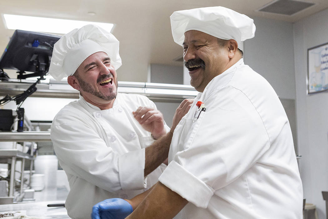 Graduates Eric Holzinger, left, and John Fierro of the Salvation Army Culinary Arts Program laugh while preparing food during preparation of the 44th graduation ceremony at the College of Southern ...