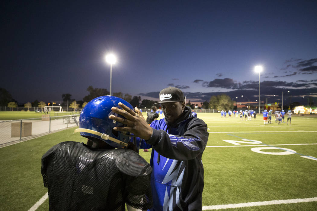 Warriors football coach Milton Burns helps J'Veon Blake with his helmet during the team's practice at a football field at Ed Fountain Park, Thursday, Nov. 2, 2017. Richard Brian Las Vegas Review-J ...
