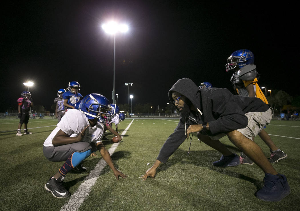 Warriors lineman Jordan Jackson, 7, gets help on his stance from assistant coach Craig Davis during the team's practice at a football field at Ed Fountain Park, Thursday, Nov. 2, 2017. Richard Bri ...