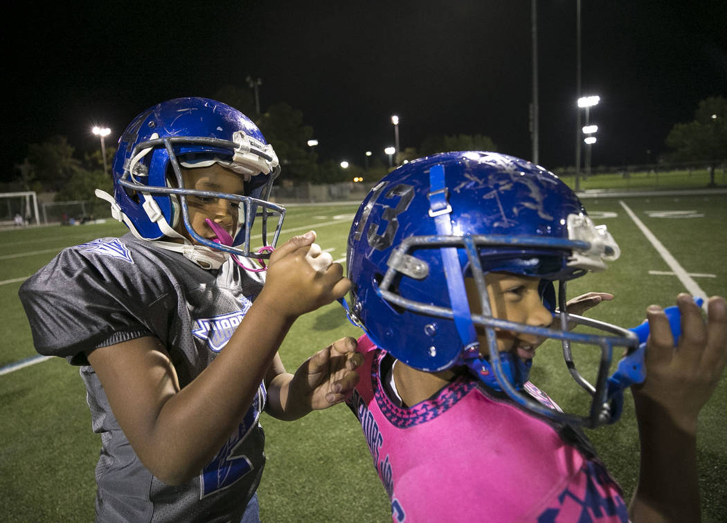 Warriors Jonathan Washington, left, 8, secures the straps on the helmet of teammate Jayden Talbot, 7, during the team's practice at a football field at Ed Fountain Park, Thursday, Nov. 2, 2017. Ri ...