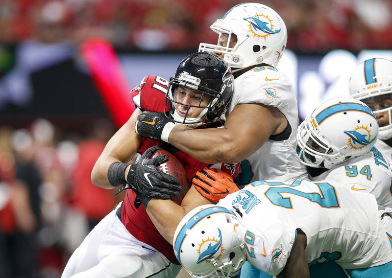 Oct 15, 2017; Atlanta, GA, USA; Atlanta Falcons tight end Austin Hooper (81) is tackled by Miami Dolphins defensive tackle Ndamukong Suh (93) and free safety Reshad Jones (20) in the third quarter ...