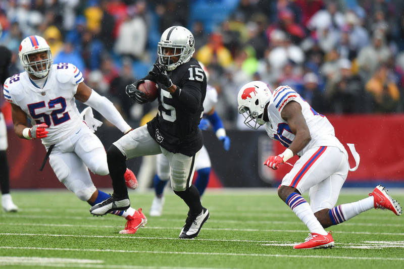 Oct 29, 2017; Orchard Park, NY, USA; Oakland Raiders wide receiver Michael Crabtree (15) runs with the ball after a catch in front of Buffalo Bills middle linebacker Preston Brown (52) during the  ...