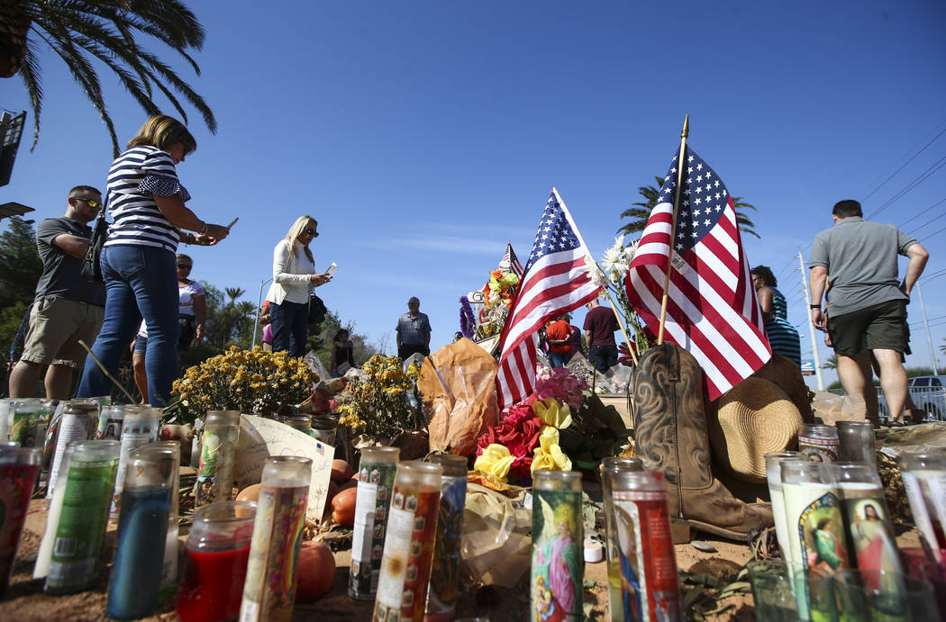 """People visit the fifty-eight crosses left in honor of the victims in the mass shooting at a makeshift memorial near the """"Welcome to Fabulous Las Vegas"""" sign in Las Vegas on Frida ..."""