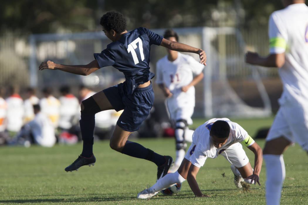 Durango's Erick Martinez-Rodriguez (8) slides for the ball against Legacy's Randolph Anderson (17) in the playoff soccer game at the Bettye Wilson Soccer Complex in Las Vegas, Thursday, Nov. 2, 20 ...