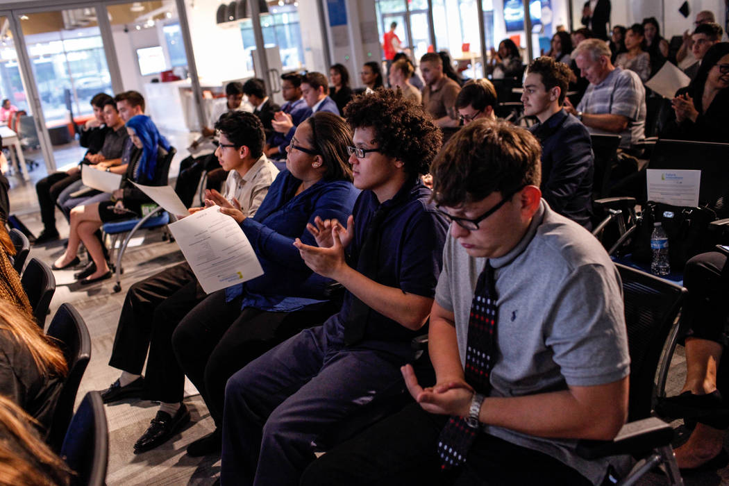 Basic High School students Filipe Deandrade, 18, second from right, and Joshua Gutierrez, 16, right, applaud during the CTA Future Innovators Business Pitch Competition at the RedFlint Experience  ...