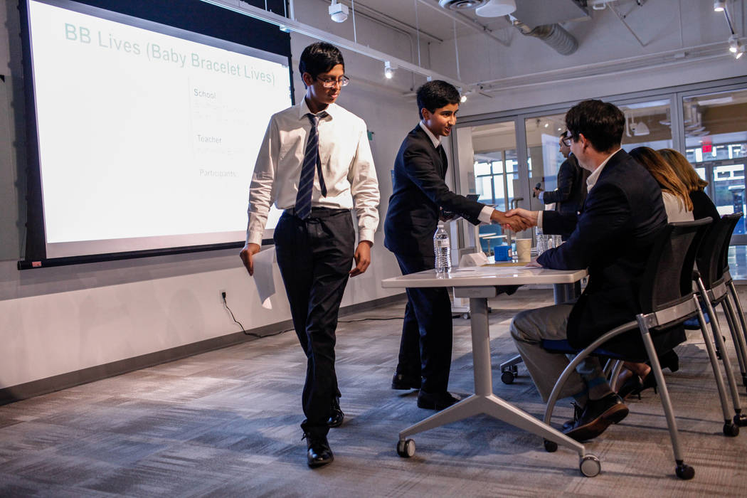Southwest Career and Technical Academy students Ishaan Raja, 15, left, and Anish Ghejerla, 15, right, shake hands with judges after presenting during the CTA Future Innovators Business Pitch Compe ...