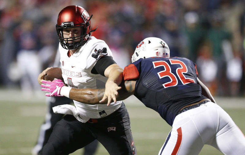 Oct 28, 2017; Fresno, CA, USA; UNLV Rebels quarterback Johnny Stanton (4) tries to avoid being tackled by Fresno State Bulldogs inside linebacker Robert Stanley (32) in the second quarter at Bulld ...
