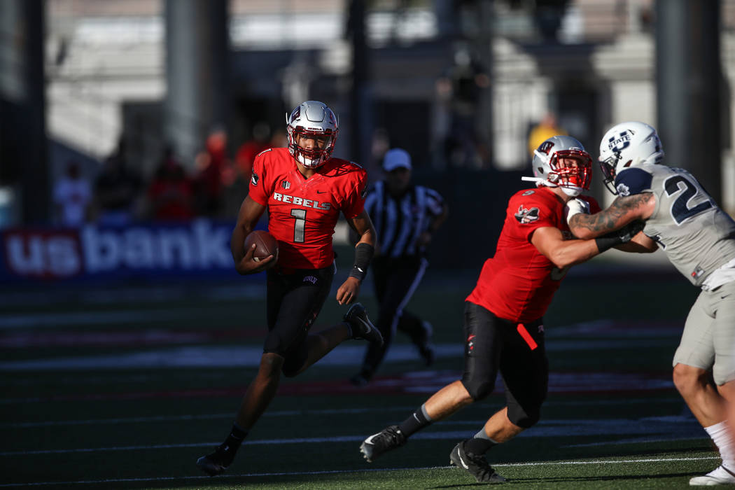 UNLV Rebels quarterback Armani Rogers (1), left, runs the ball against the Utah State Aggies during the second quarter of a football game at Sam Boyd Stadium in Las Vegas, Saturday, Oct. 21, 2017. ...