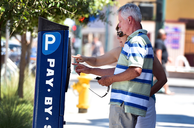Tourists Marv and Jean Junk of Iowa feed a parking meter along 7th Street in downtown Las Vegas on Friday, June 12, 2015. (David Becker/Las Vegas Review-Journal)