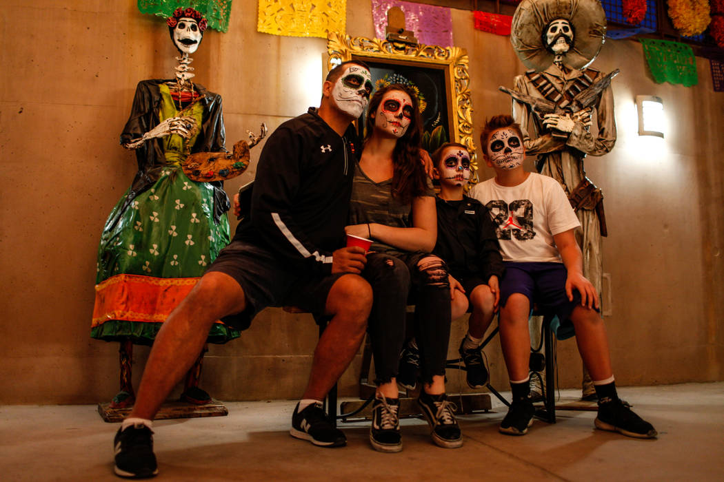Mark Latimer, 46, left, sits next to his children Sydney, 16, second from left, Maddox, 7, second from right, and Teddy, 12, right, during a Dia de los Muertos event at Springs Preserve in Las Veg ...
