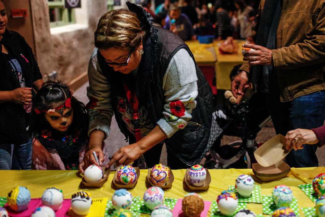 Everly Roa, 5, left, and Nicole Parra, 49, right, both of Las Vegas, place their decorated sugar skulls on display during a Dia de los Muertos event at Springs Preserve in Las Vegas, Sunday, Nov.  ...