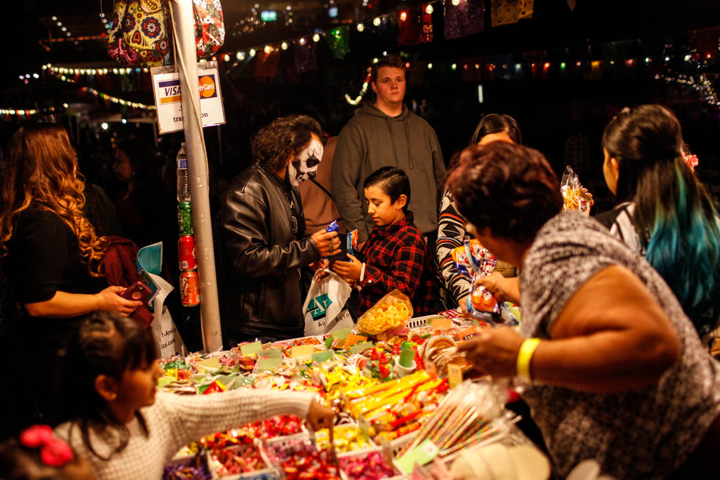 Israel Lazo of Las Vegas, 40, left, buys his son David, 9, right, candy during a Dia de los Muertos event at Springs Preserve in Las Vegas, Sunday, Nov. 5, 2017. Joel Angel Juarez Las Vegas Review ...