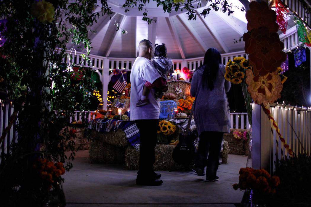Alberto Valenzuela of Las Vegas, 35, holds his daughter Aylani, 1, as they look at an altar during a Dia de los Muertos event at Springs Preserve in Las Vegas, Sunday, Nov. 5, 2017. Joel Angel Jua ...