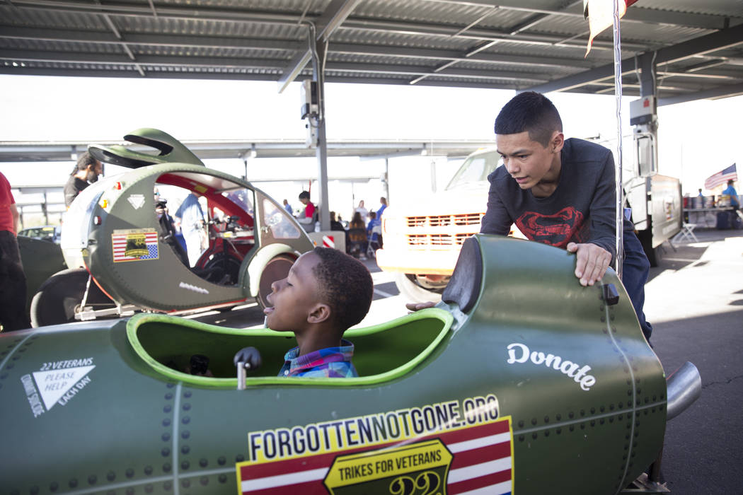 Terrell Moseley Jr., left, 10, with the help of Dawnavon Carreon, 15, rides a trike during the 3rd Annual Car Show and BBQ in celebration of Veterans Day at the VA Southern Nevada Healthcare Syste ...