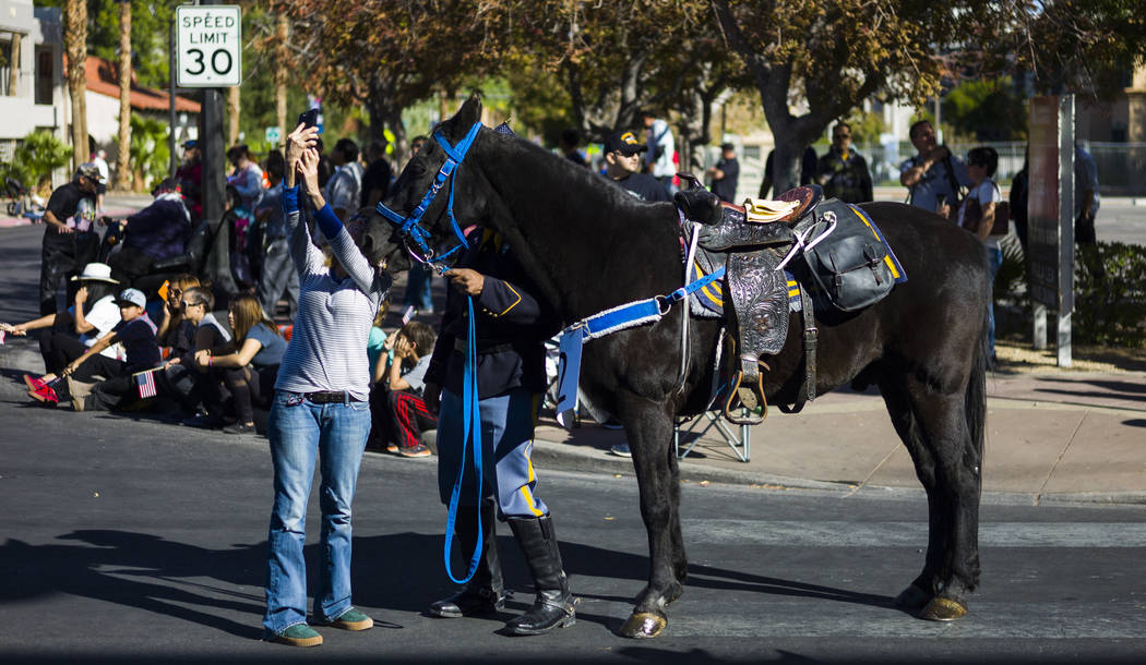 A woman takes a selfie with a parade participant before the start of the Veterans Day Parade in downtown Las Vegas on Saturday, Nov. 11, 2017. Chase Stevens Las Vegas Review-Journal @csstevensphoto