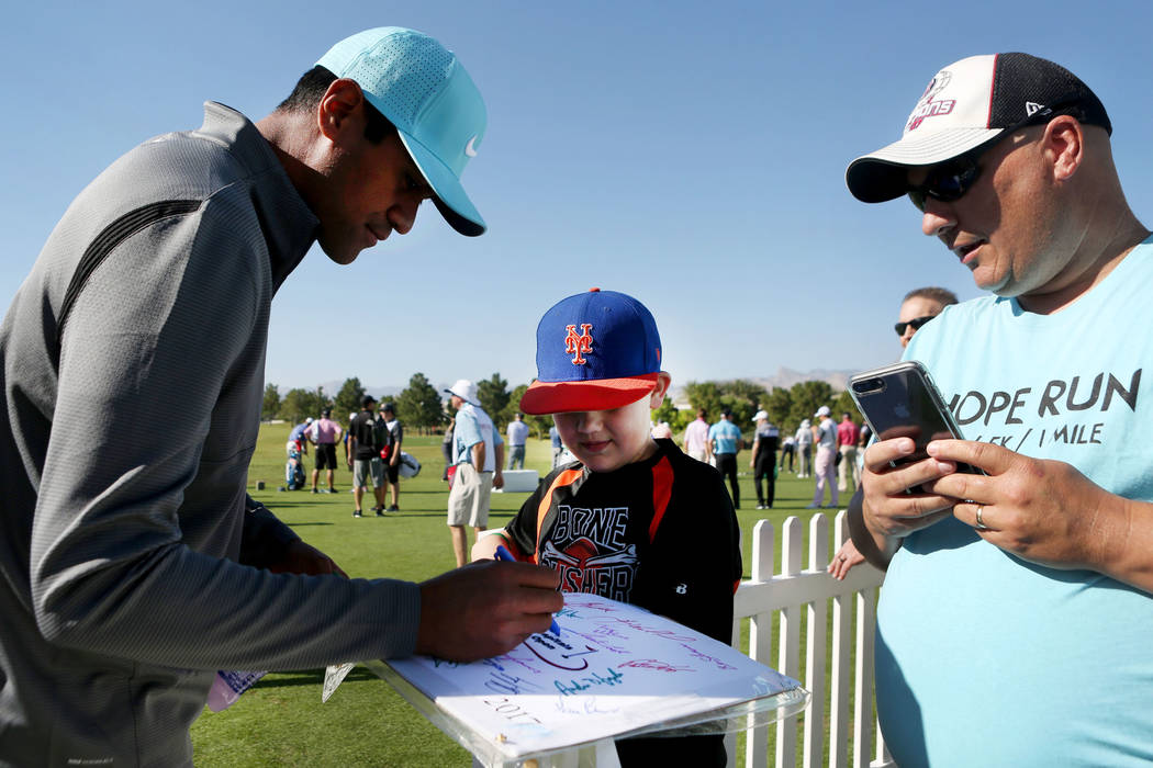 American professional golfer Tony Finau, left, signs his autograph for Jonathan Mackenzie, 10, left and Bob Mackenzie during the preview day of the Shriners Hospitals for Children Open, PGA Tour a ...