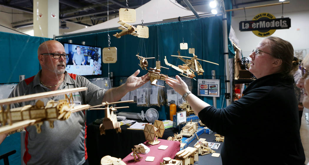 Exhibitor Craig Matheny, California, with LazerModels, makes a sale of his hand cut unique laser cut wood model kits to Veronica Peterson, Las Vegas, during the final day of the 2017 Craft Festiva ...