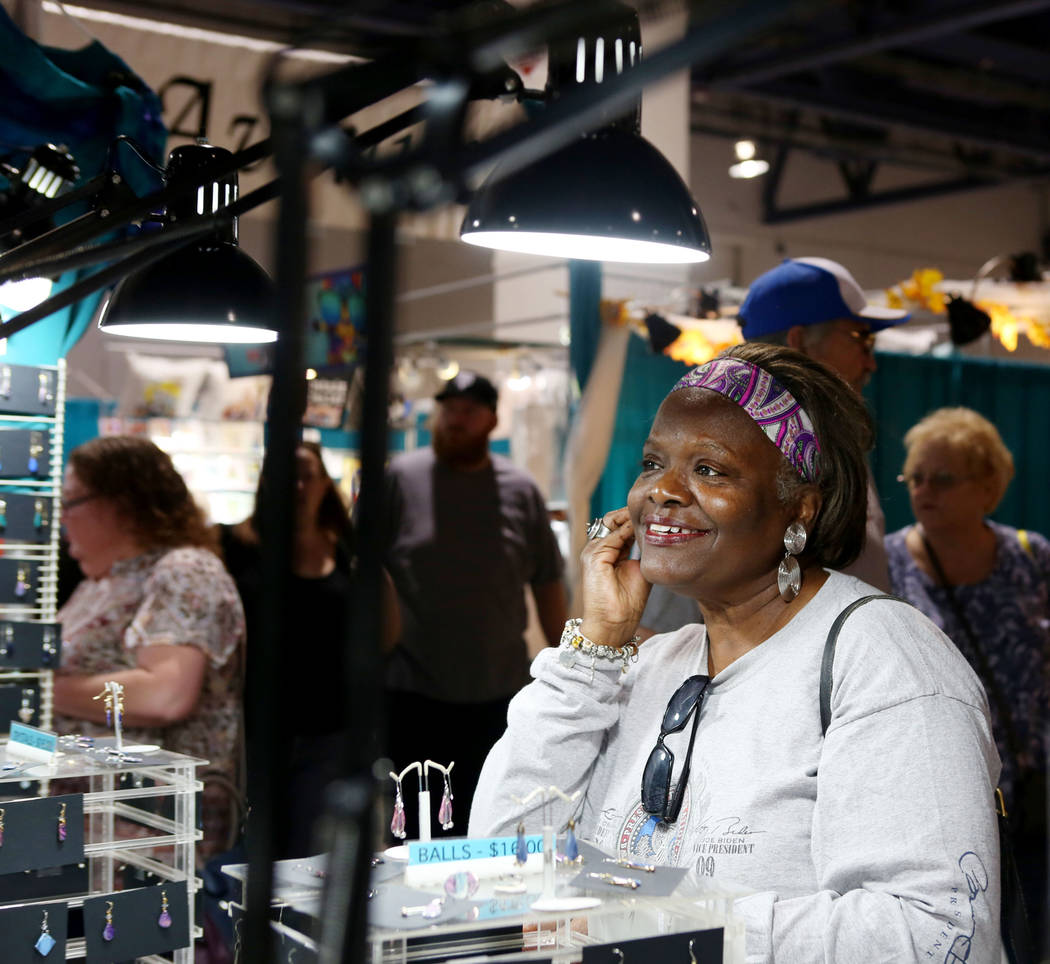Linda Ammons, Las Vegas, tries on a pair of Karen Nolke Collections earrings during the final day of the 2017 Craft Festival at the Cashman Center in Las Vegas, Sunday, Nov. 5, 2017. Elizabeth Bru ...