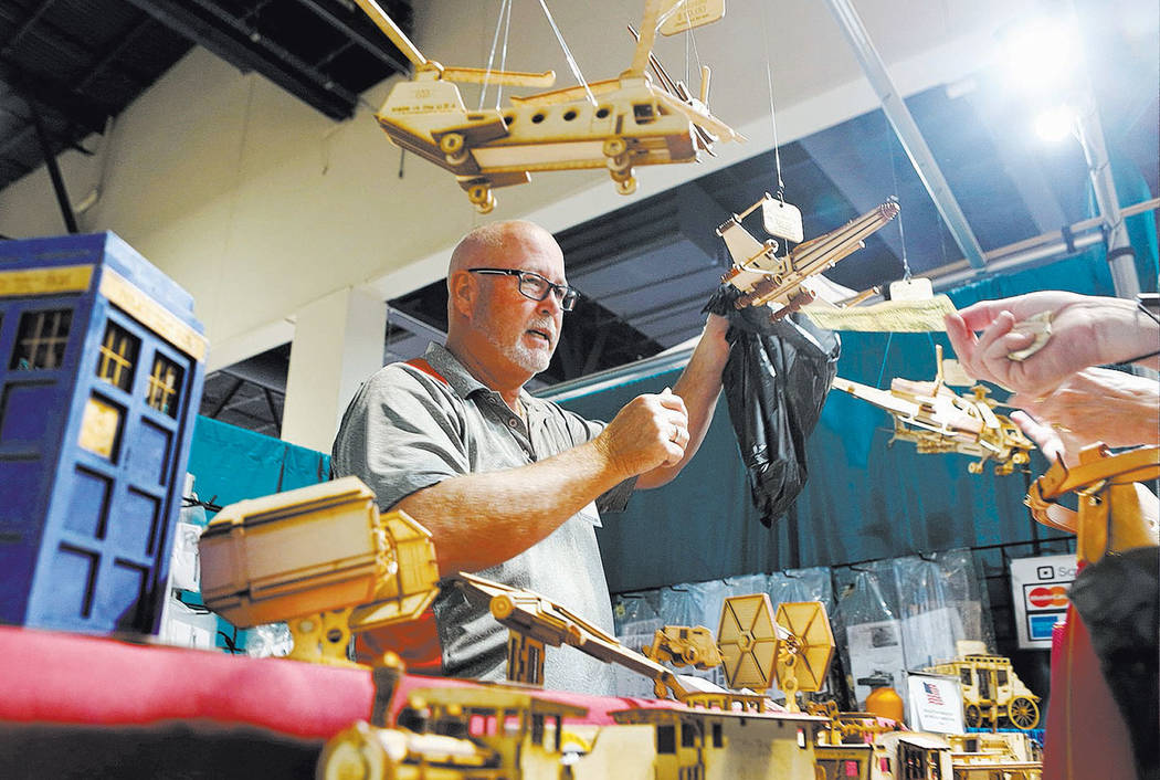 Exhibitor Craig Matheny with LazerModels makes a sale at his booth of hand cut unique laser cut wood model kits during the final day of the 2017 Craft Festival at the Cashman Center in Las Vegas,  ...