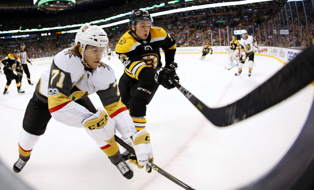 In this photo taken with a fisheye lens, Vegas Golden Knights' William Karlsson, left, battles in the corner with Boston Bruins' Charlie McAvoy during the first period of an NHL hockey game in Bos ...