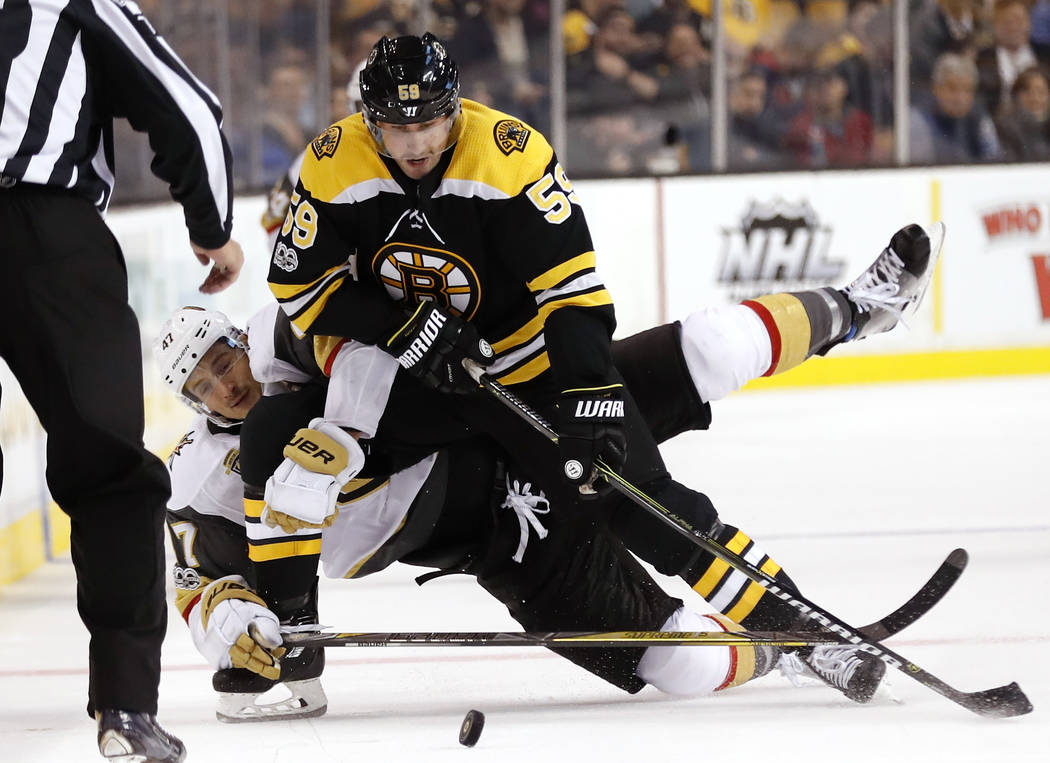 Boston Bruins' Tim Schaller (59) battles Vegas Golden Knights' Luca Sbisa for the puck during the second period of an NHL hockey game in Boston, Thursday, Nov. 2, 2017. (AP Photo/Winslow Townson)