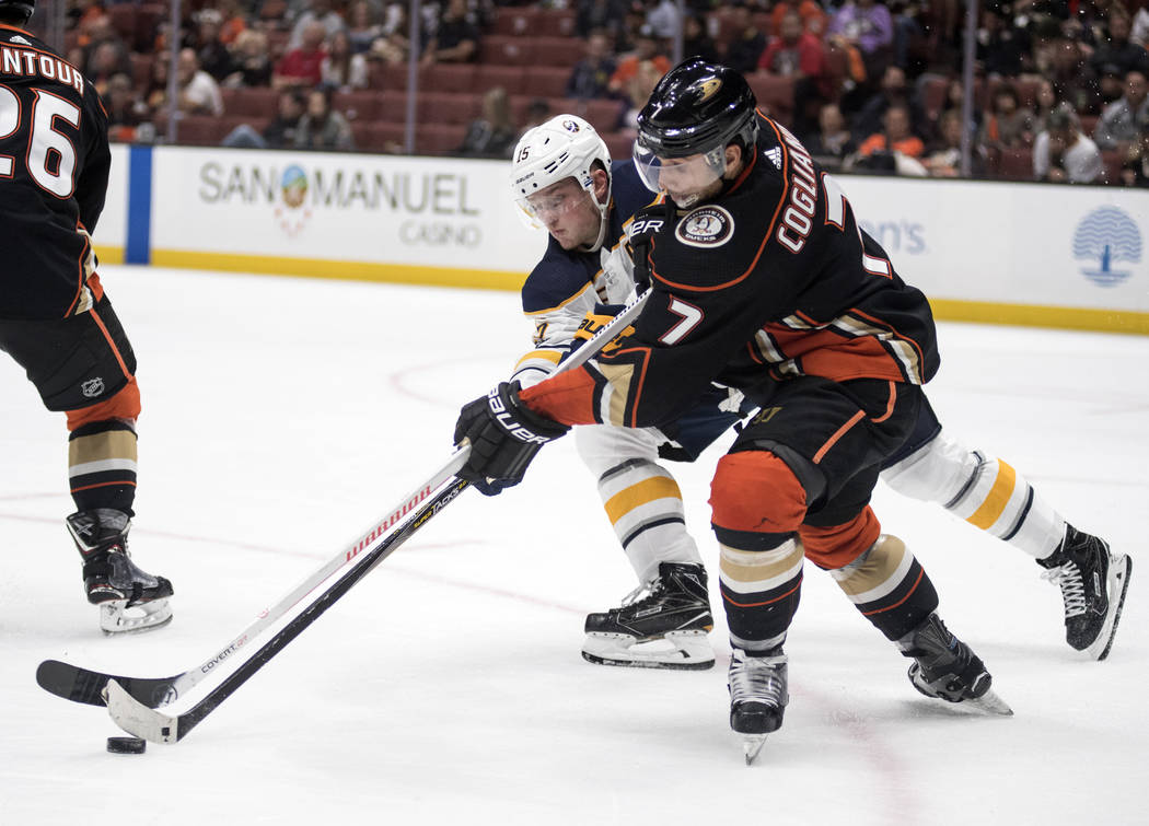 Anaheim Ducks left wing Andrew Cogliano, right, and Buffalo Sabres center Jack Eichel battle for the puck during the third period of an NHL hockey game in Anaheim, Calif., Sunday, Oct. 15, 2017. ( ...