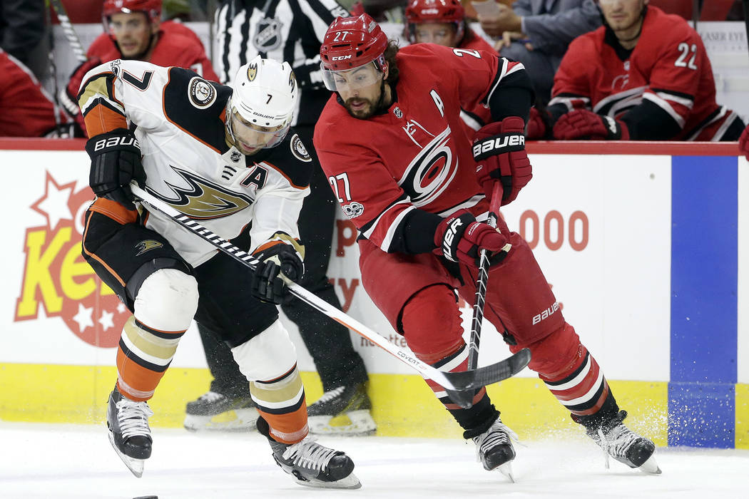 Anaheim Ducks' Andrew Cogliano (7) and Carolina Hurricanes' Justin Faulk (27) chase the puck during the first period of an NHL hockey game in Raleigh, N.C., Sunday, Oct. 29, 2017. (AP Photo/Gerry  ...