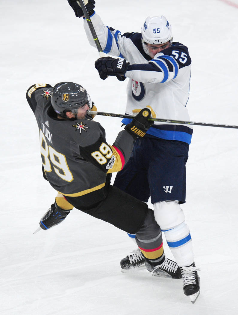 Winnipeg Jets foward Mark Scheifele (55) delivers a crushing hit on VegasnGolden Knights forward Alex Tuch in the second period of their NHL hockey game at T-Mobile Arena in Las Vegas Friday Novem ...