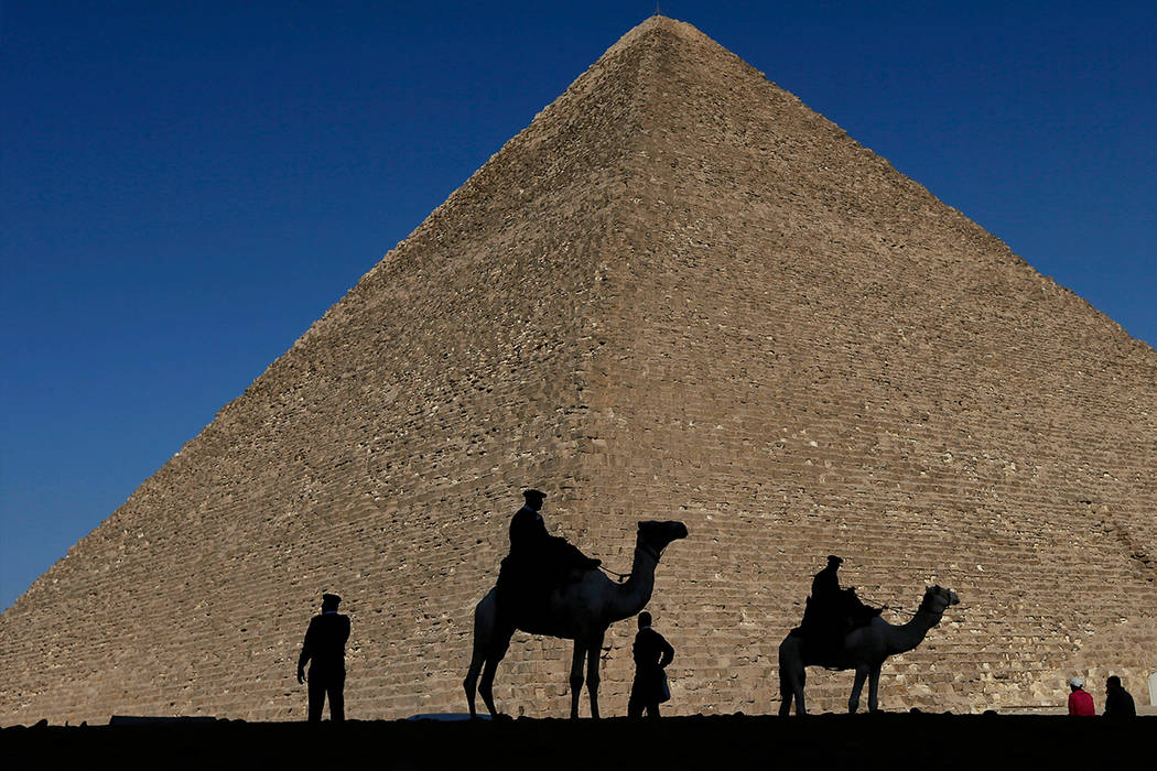 In this Dec. 12, 2012 file photo, policemen are silhouetted against the Great Pyramid in Giza, Egypt. Scientists have found a previously undiscovered hidden chamber in Egypt's Great Pyramid of Giz ...