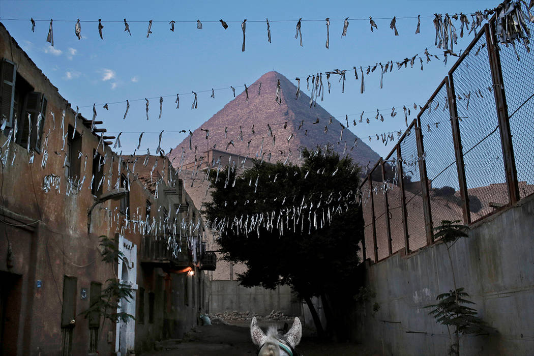 In this Nov. 17, 2016 file photo, a horse walks near the Great Pyramid, in Giza, Egypt. Scientists have found a previously undiscovered hidden chamber in Egypt's Great Pyramid of Giza, the first s ...