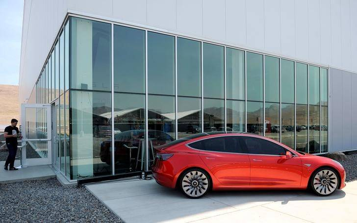 A prototype of the Tesla Model 3 is on display in front of the factory during a media tour of the Tesla Gigafactory which will produce batteries for the electric carmaker in Sparks, Nevada, U.S. J ...
