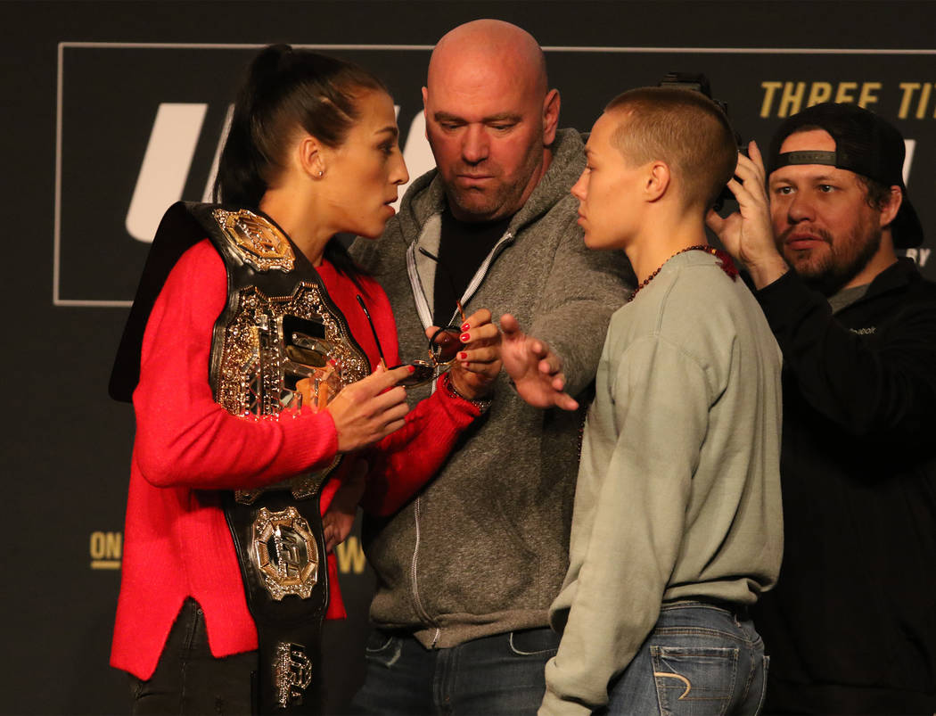 UFC strawweight champion Joanna Jedrzejczyk, left, stares down Rose Namajunas, right, as UFC president Dana White separates them during a staredown at the UFC 217 news conference at Madison Square ...