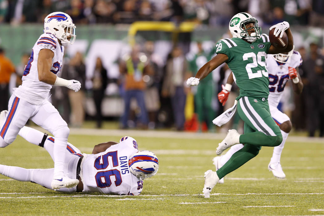 New York Jets running back Bilal Powell, right, avoids being tripped up by Buffalo Bills defensive end Ryan Davis (56) on a long run during the second half of an NFL football game, Thursday, Nov.  ...