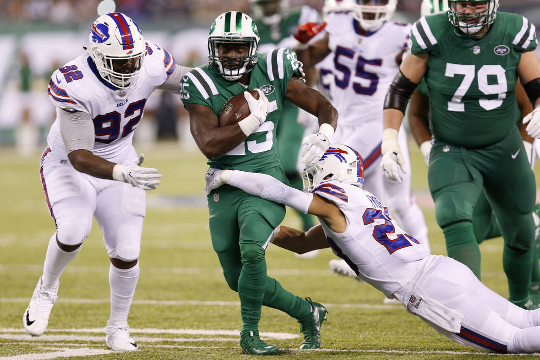 New York Jets running back Elijah McGuire (25) runs with the ball as Buffalo Bills strong safety Micah Hyde (23) and defensive tackle Adolphus Washington (92) tried to bring him down during the se ...