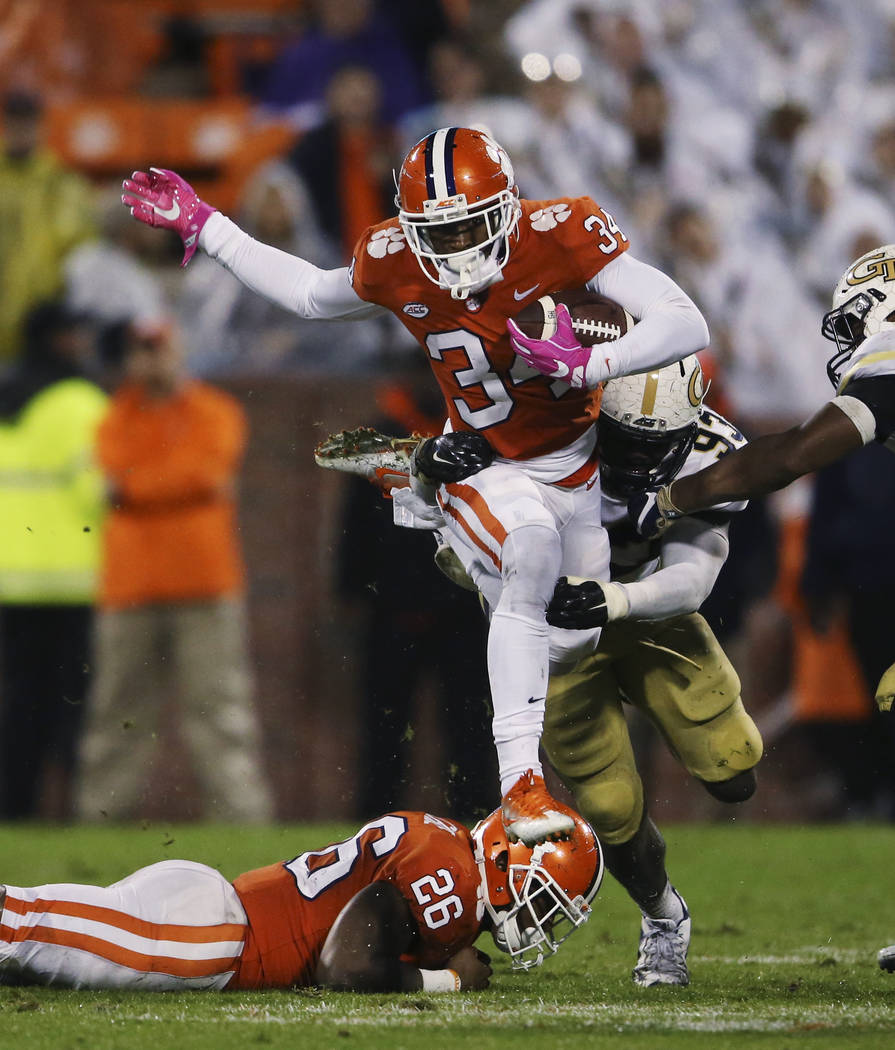 Clemson wide receiver Ray-Ray McCloud (34) tries to break free from Georgia Tech defensive lineman Antonio Simmons (93) in the second half of an NCAA college football game Saturday, Oct. 28, 2017, ...