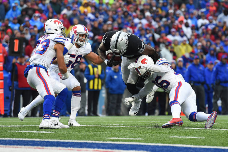Oct 29, 2017; Orchard Park, NY, USA; Oakland Raiders tight end Jared Cook (87) goes airborne while being hit by Buffalo Bills defensive back Trae Elston (36) during the fourth quarter at New Era F ...