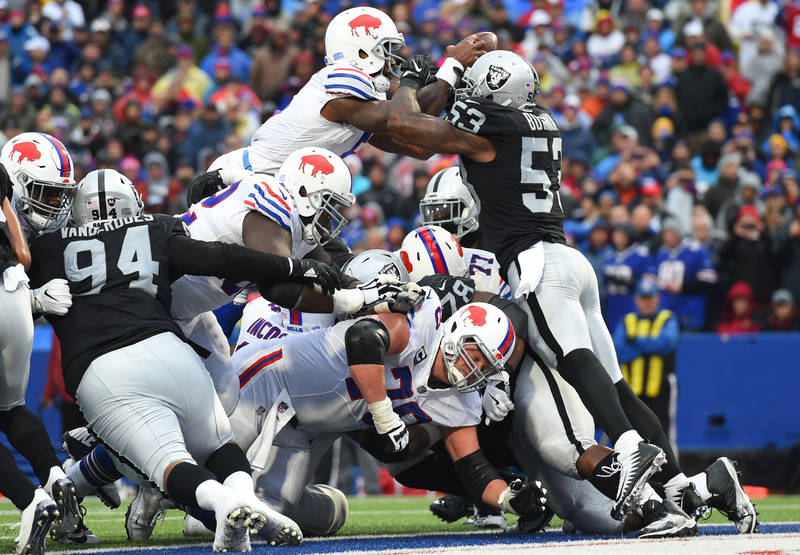 Oct 29, 2017; Orchard Park, NY, USA; Buffalo Bills quarterback Tyrod Taylor (5) leaps into the end zone for a touchdown while being hit by Oakland Raiders middle linebacker NaVorro Bowman (53) dur ...