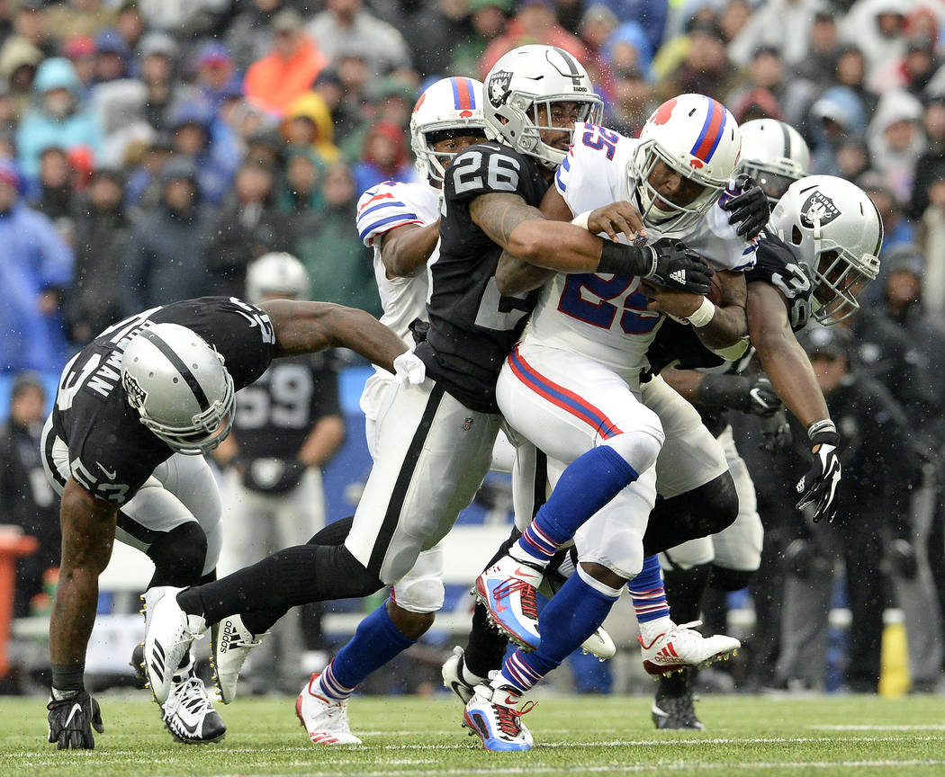Buffalo Bills running back LeSean McCoy (25) runs with the ball as Oakland Raiders middle linebacker NaVorro Bowman (53), safety Shalom Luani (26) and cornerback T.J. Carrie (38) try to bring him  ...