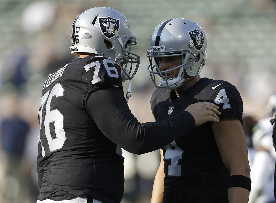Oakland Raiders offensive guard Jon Feliciano (76) talks with quarterback Derek Carr (4) before an NFL preseason football game against the Seattle Seahawks in Oakland, Calif., Thursday, Aug. 31, 2 ...
