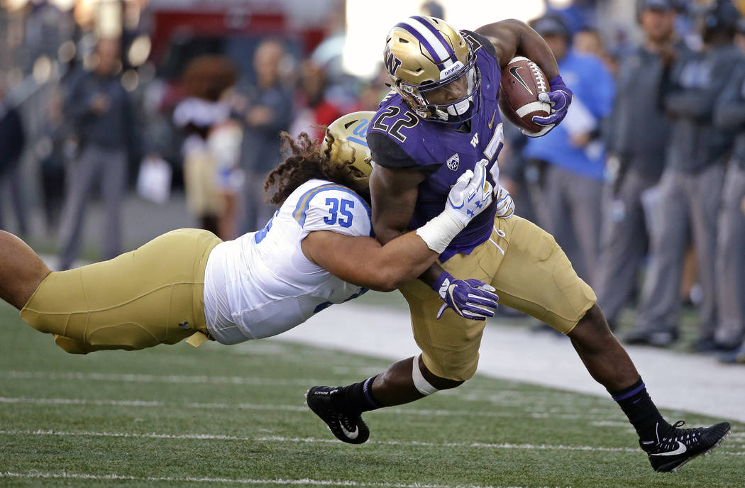 UCLA's Ainuu Taua (35) dives to bring down Washington's Lavon Coleman in the second half of an NCAA college football game Saturday, Oct. 28, 2017, in Seattle. (AP Photo/Elaine Thompson)