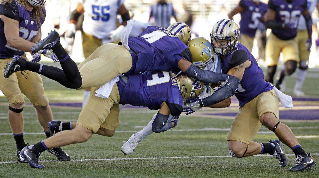 UCLA's Chris Pabico, second from right, is brought down by Washington's Austin Joyner (4), Elijah Molden (3) and Taylor Rapp in the second half of an NCAA college football game Saturday, Oct. 28,  ...