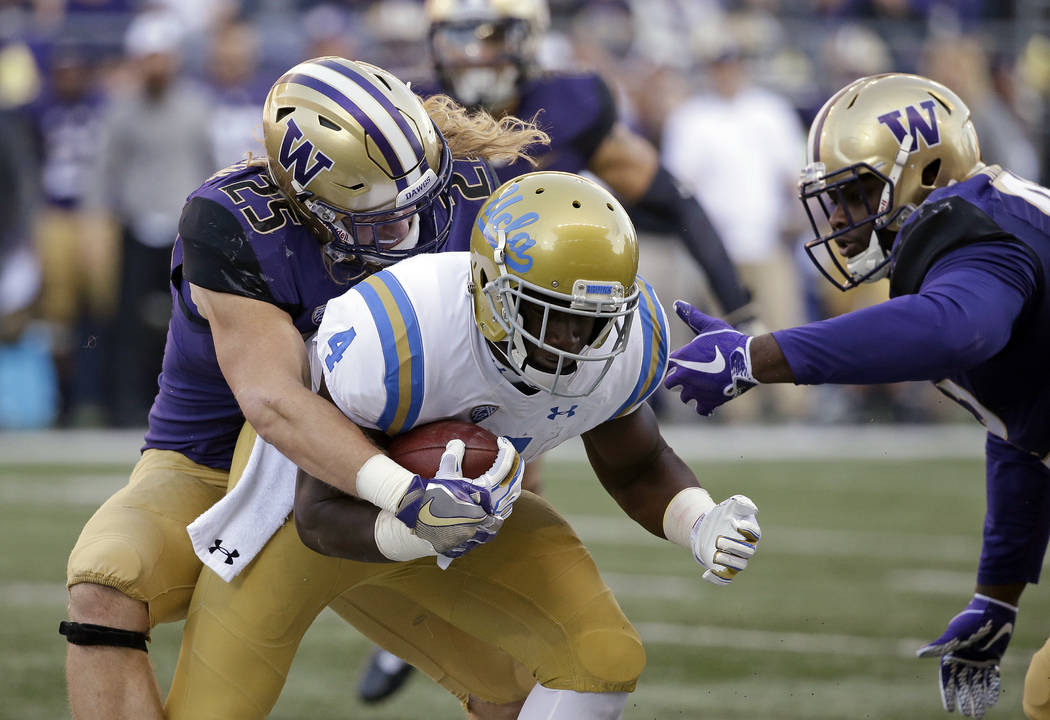 UCLA's Bolu Olorunfunmi (4) is brought down by Washington's Ben Burr-Kirven (25) and Jaylen Johnson in the first half of an NCAA college football game Saturday, Oct. 28, 2017, in Seattle. (AP Phot ...