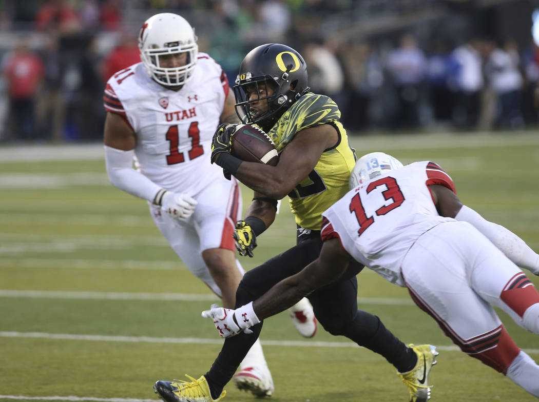 Oregon running back Kani Benoit, center, runs between Utah's Kylie Fitts, left, and Marquise Blair on his way to a touchdown during the fourth quarter of an NCAA college football game Saturday, Oc ...