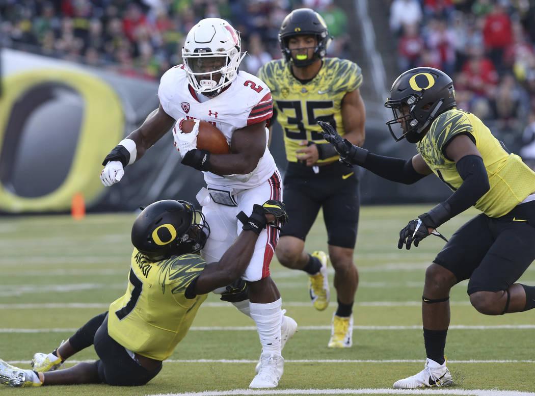 Oregon's Oregon cornerback Ugochukwu Amadi, left, works to pull down Utah running back Zach Moss with Oregon linebacker Troy Dye and cornerback Thomas Graham Jr. in pursuit during the third quarte ...