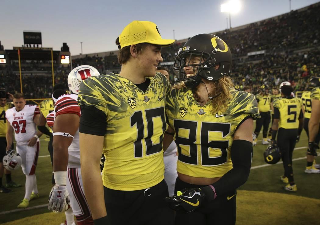Injured Oregon quarterback Justin Herbert, left, celebrates with teammate Oregon wide receiver Brenden Schooler after an NCAA college football game against Utah Saturday, Oct. 28, 2017, in Eugene, ...